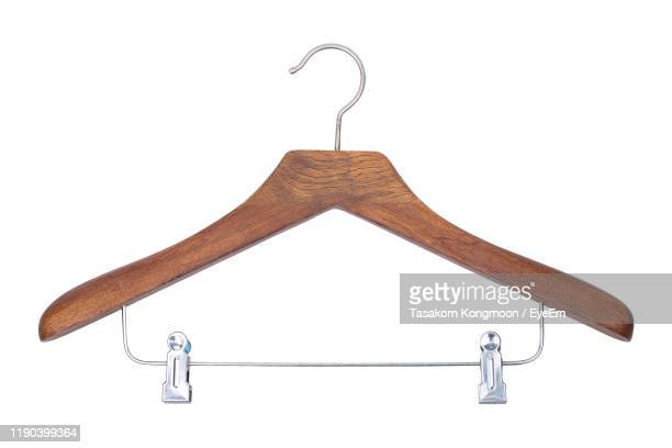 close-up of coathanger against white background - coathanger stock pictures, royalty-free photos & images