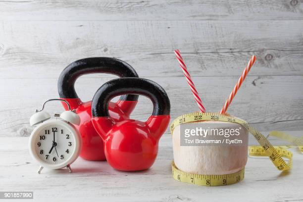 close-up of coconut by kettlebell and clock on table - coconut water stock pictures, royalty-free photos & images