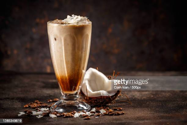 close-up of coconut flavored coffee drink with whipped cream on table - coffee drink stock pictures, royalty-free photos & images