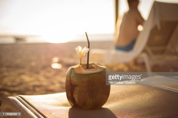 close-up of coconut on lounge chair at beach during sunset - ile maurice photos et images de collection
