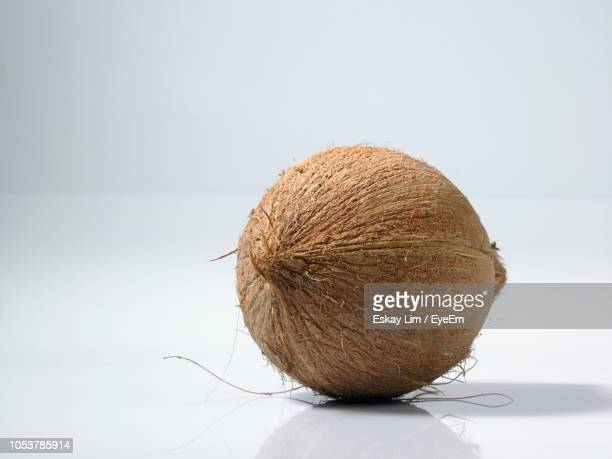 Close-Up Of Coconut On Table Against White Background