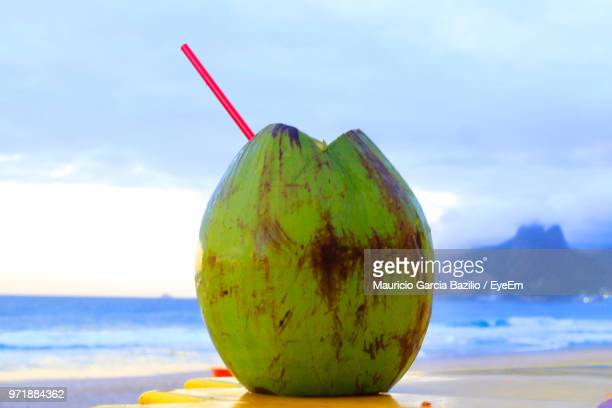 close-up of coconut on table at beach against sky - coconut water stock pictures, royalty-free photos & images