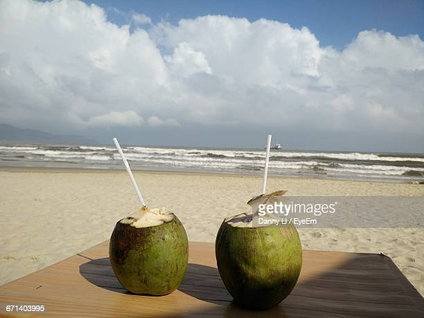 Close-Up Of Coconuts Drinks Against Beach