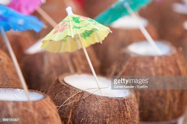 Close-Up Of Coconuts With Drink Umbrellas