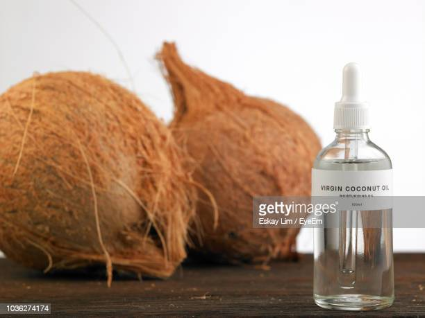 close-up of coconuts with oil against white background on table - coconut oil stock pictures, royalty-free photos & images