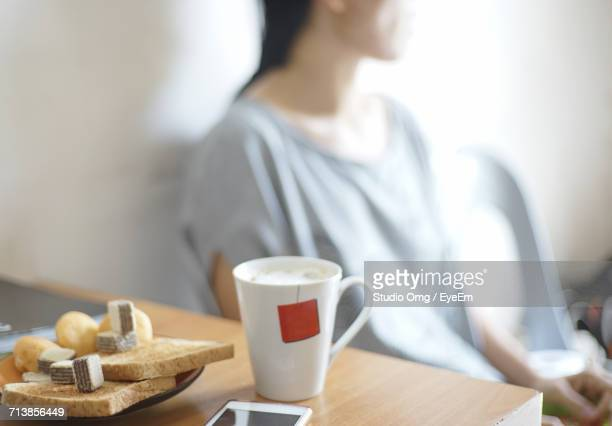 Close-Up Of Coffee And Food On Table While Woman Sitting On Chair Against Wall