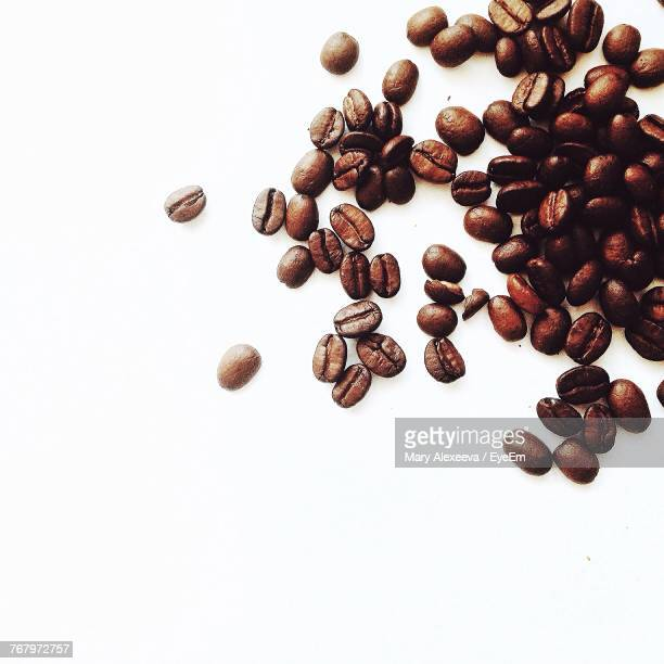 close-up of coffee beans against white background - coffee beans stock photos and pictures