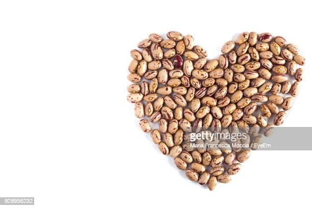 Close-Up Of Coffee Beans Arranged In Heart Shape Against White Background