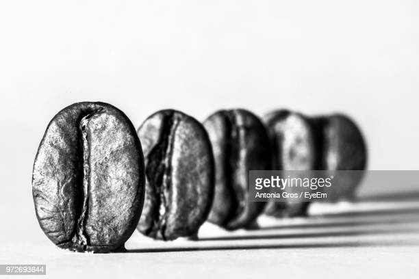 Close-Up Of Coffee Beans Arranged Over White Background