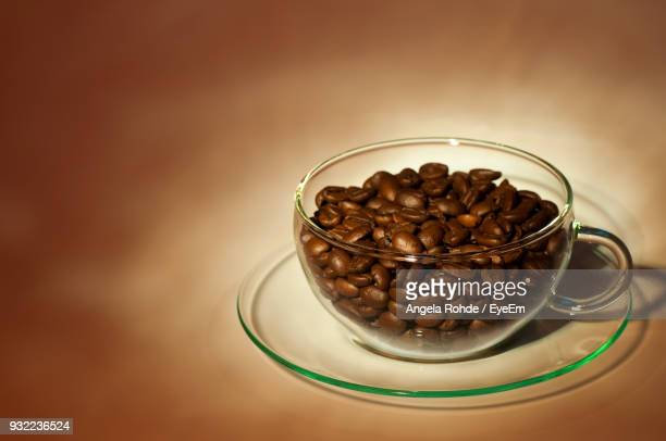 close-up of coffee beans in cup against brown background - angela rohde stock-fotos und bilder
