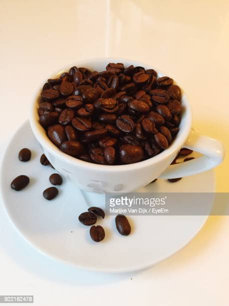 Close-Up Of Coffee Beans In Cup On Table
