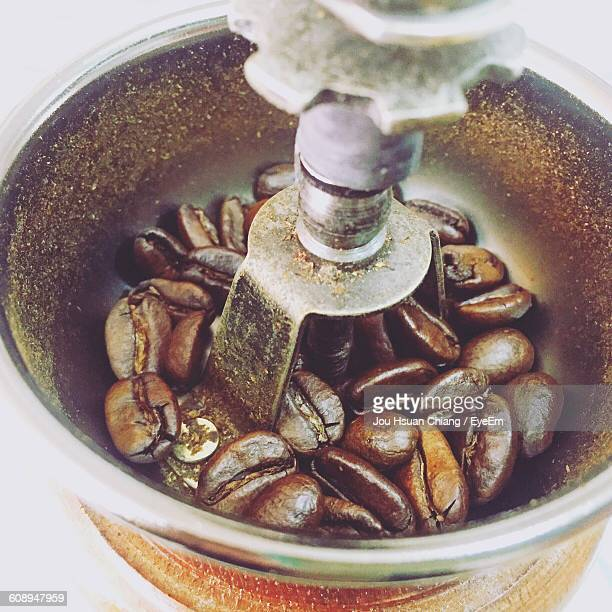 close-up of coffee beans in grinder - coffee grinder stock photos and pictures