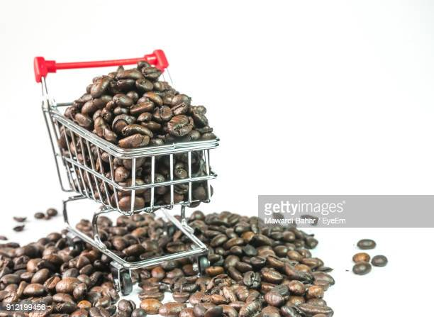Close-Up Of Coffee Beans In Shopping Cart Against White Background