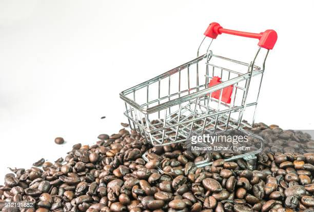 Close-Up Of Coffee Beans With Shopping Cart Against White Background