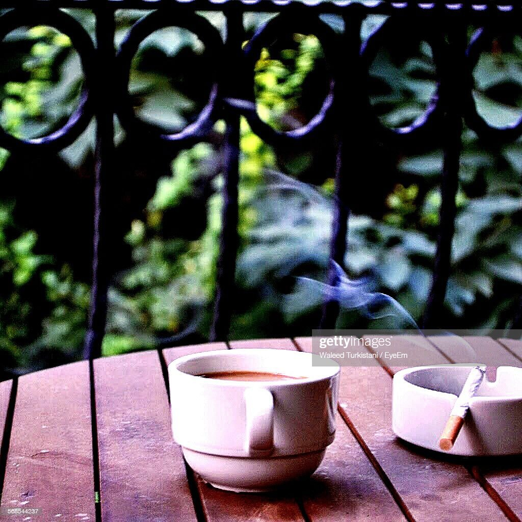 Close-Up Of Coffee Besides Burning Cigarette On Table In Balcony : Stock Photo