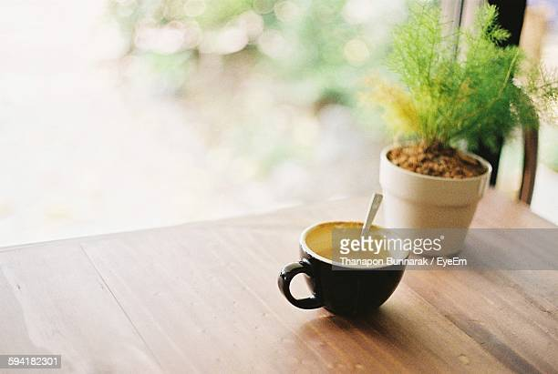 Close-Up Of Coffee By Potted Plant On Table