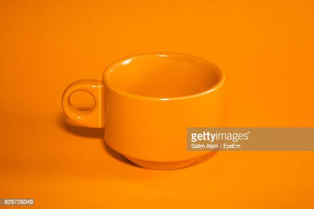 Close-Up Of Coffee Cup Against Orange Background