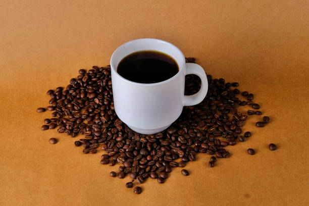 Close-Up Of Coffee Cup And Beans On Brown Background