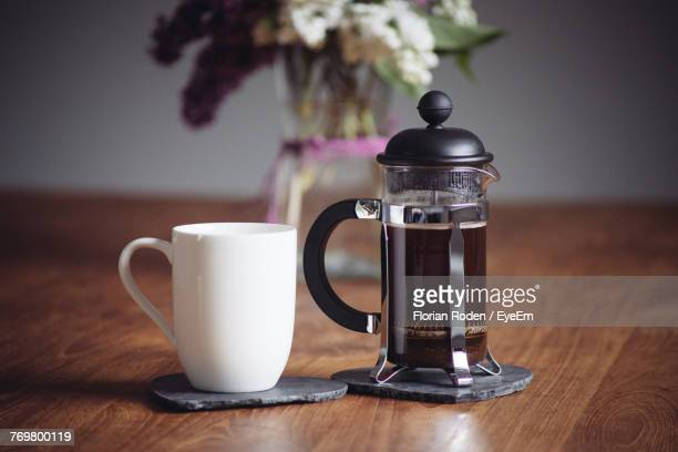 close-up of coffee cup and french press on table - coffee maker stock pictures, royalty-free photos & images