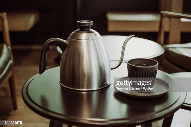 close-up of coffee cup and kettle on table at home - nikitina stock pictures, royalty-free photos & images