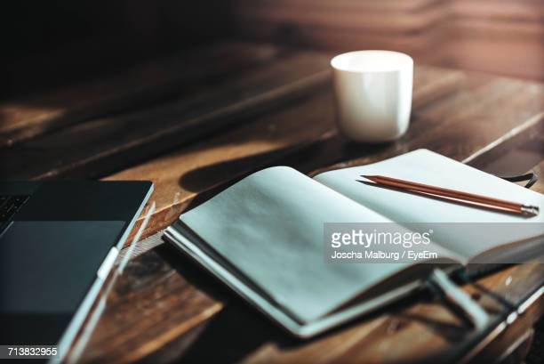 Close-Up Of Coffee Cup And Notebook On Table