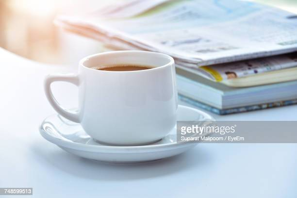 Close-Up Of Coffee Cup By Books And Newspaper On Table