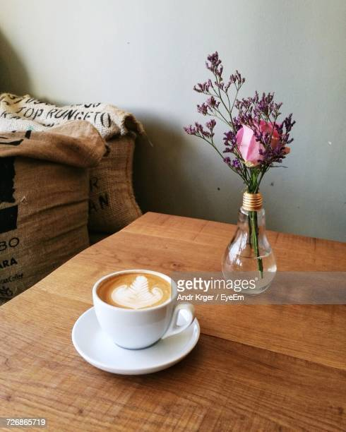 Close-Up Of Coffee Cup By Flower Vase On Wooden Table