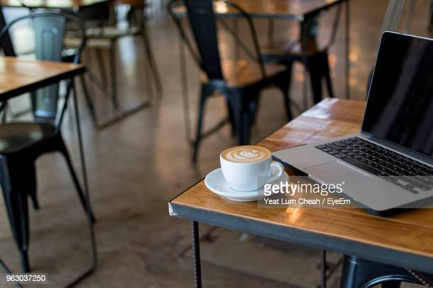 close-up of coffee cup by laptop on table in cafe - tavolino foto e immagini stock