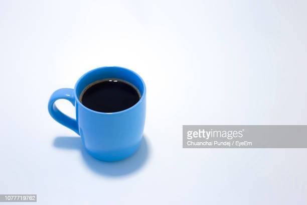 close-up of coffee cup in blue mug on white background - マグカップ ストックフォトと画像