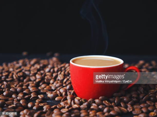 Close-Up Of Coffee Cup On Beans Against Black Background