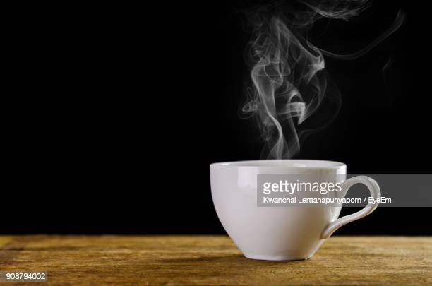 close-up of coffee cup on table against black background - kaffee getränk stock-fotos und bilder