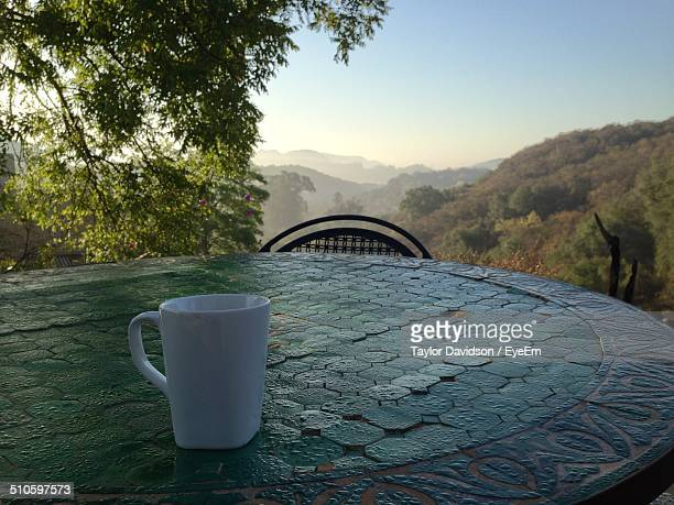 Close-up of coffee cup on table against landscape