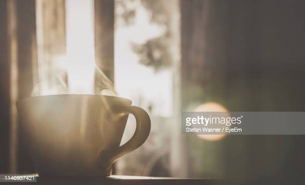 close-up of coffee cup on table against window - morning stockfoto's en -beelden