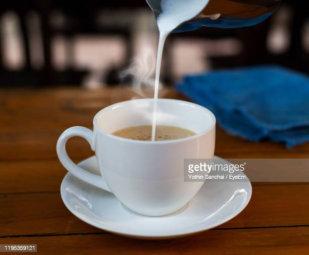close-up of coffee cup on table - cream dairy product stock pictures, royalty-free photos & images