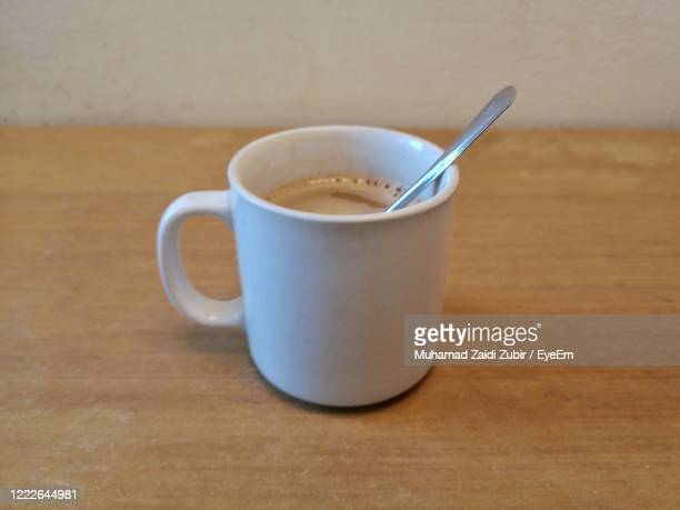 close-up of coffee cup on table - ティースプーン ストックフォトと画像
