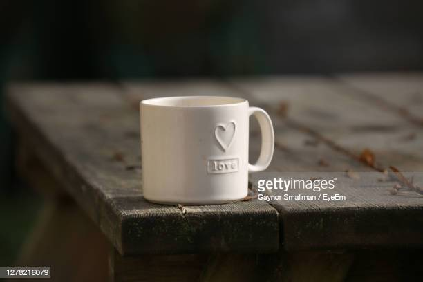 close-up of coffee cup on table - wood material stock pictures, royalty-free photos & images