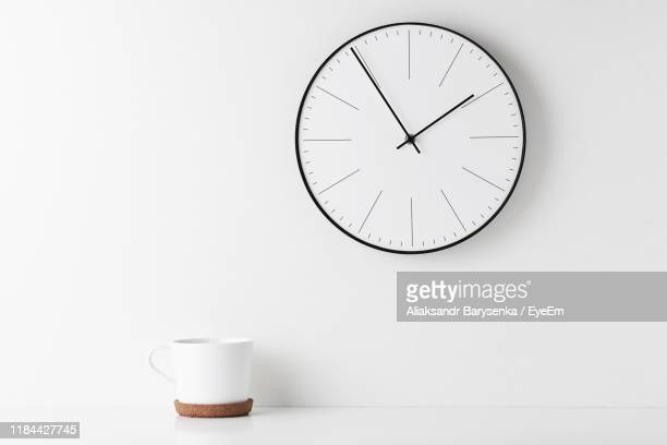 close-up of coffee cup on table wall with clock - klok stockfoto's en -beelden