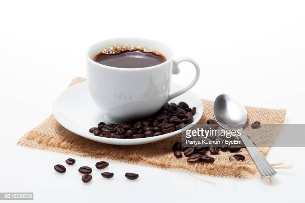 Close-Up Of Coffee Cup With Beans Over White Background