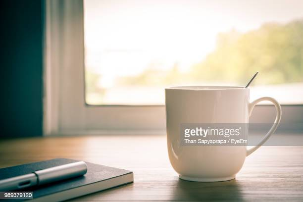 close-up of coffee cup with diary and pen on table by window - mug stock pictures, royalty-free photos & images