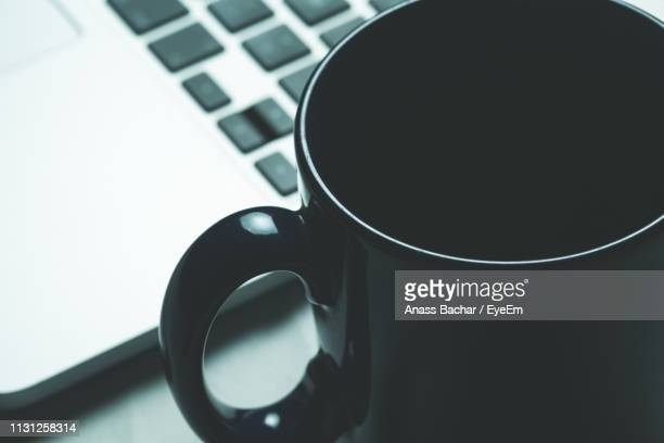 Close-Up Of Coffee Cup With Laptop On Table