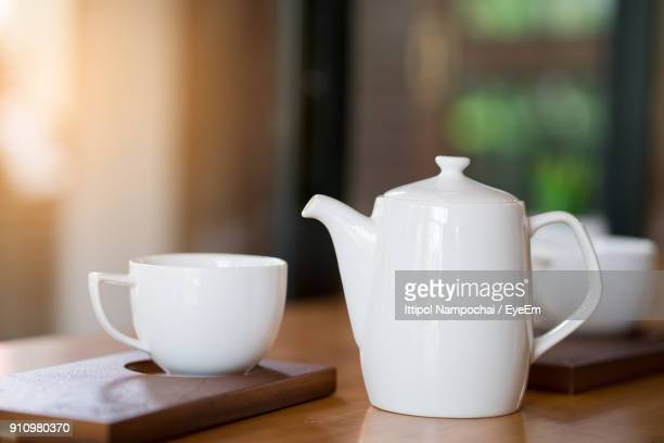 close-up of coffee cup with teapot on table - ティーポット ストックフォトと画像
