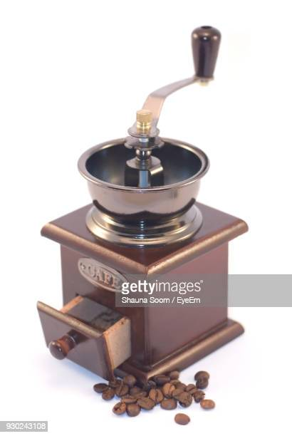 close-up of coffee grinder and beans over white background - coffee grinder stock photos and pictures