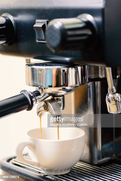 Close-Up Of Coffee Maker Pouring Drink In Cup