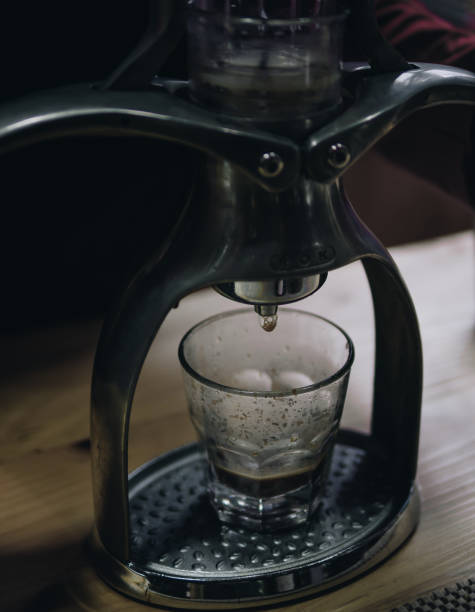 Close-Up Of Coffee Pouring From Machinery In Glass