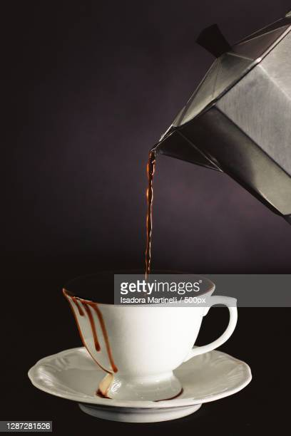 close-up of coffee pouring in cup against black background - martinelli stock pictures, royalty-free photos & images