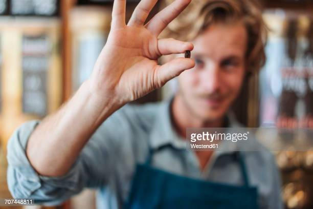 close-up of coffee roaster in his shop holding coffee bean - man made stock pictures, royalty-free photos & images