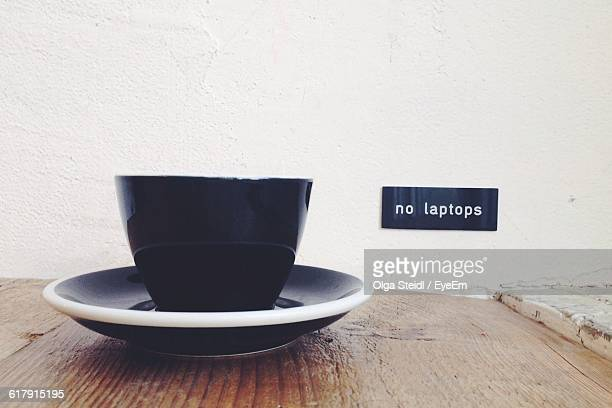 Close-Up Of Coffee Served On Table Against White Wall