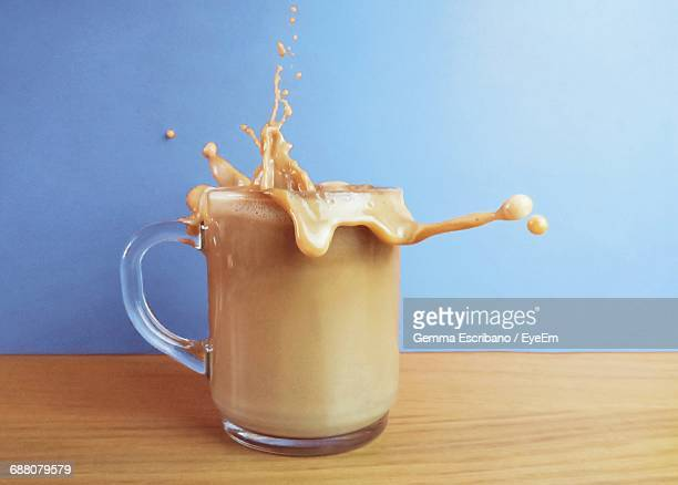 Close-Up Of Coffee Splashing From Cup On Wooden Table Against Wall