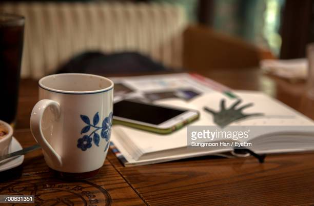 Close-Up Of Coffee With Book Mobile Phone On Wooden Table