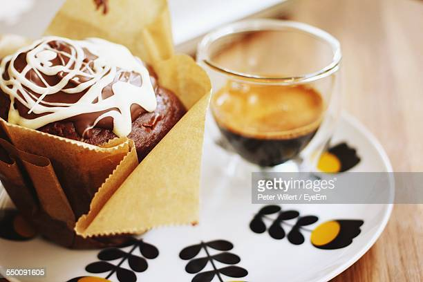 Close-Up Of Coffee With Muffin Served On Table